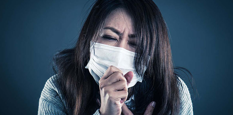 A woman is wearing a mouth mask and coughing into her hand