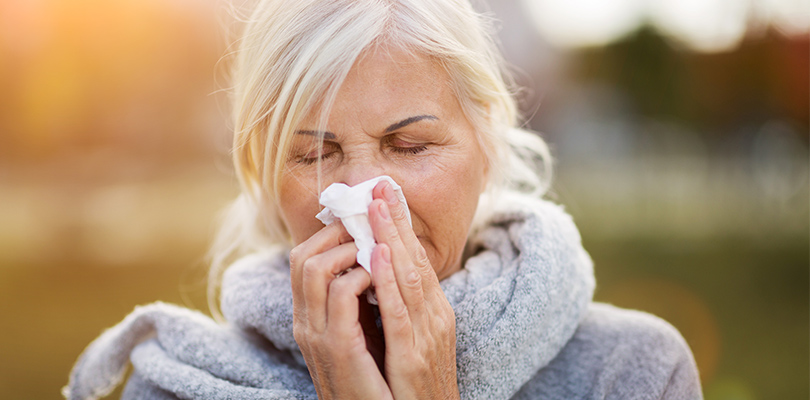 Older woman outside blowing her nose