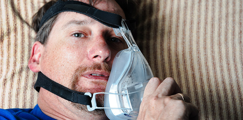 Man taking a BiPAP mask off his face