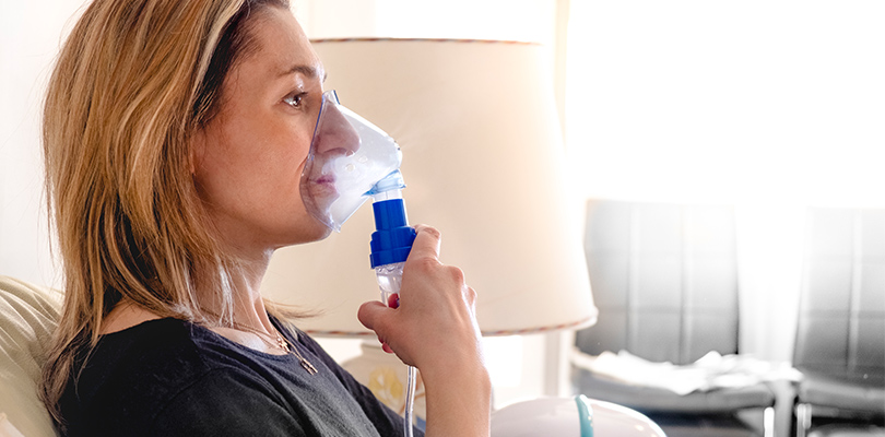 Woman holding an oxygen mask to her face